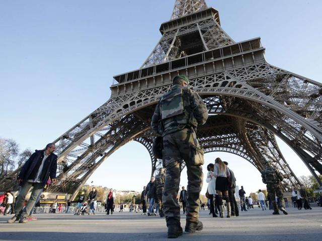 A soldier patrols in front of the Eiffel Tower in Paris.