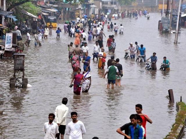 Chennai: People wade through a waterlogged road following heavy rains at Vyasarpadi in Chennai on Friday. TN