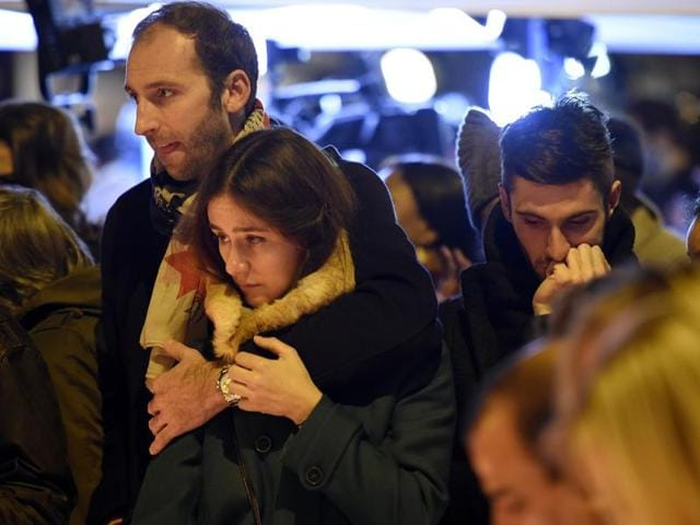 People gather at a makeshift memorial in front of the Bataclan theatre, one of the site of the attacks in Paris, on November 15, 2015, in Paris. Islamic State jihadists claimed a series of coordinated attacks by gunmen and suicide bombers in Paris that killed at least 132 people in scenes of carnage at a concert hall, restaurants and the national stadium.AFP PHOTO / FRANCK FIFE
