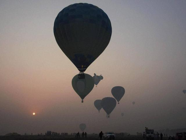 Hot air balloons fly around the Taj Mahal during the international balloon festival 2015 on the banks of the Yamuna river.