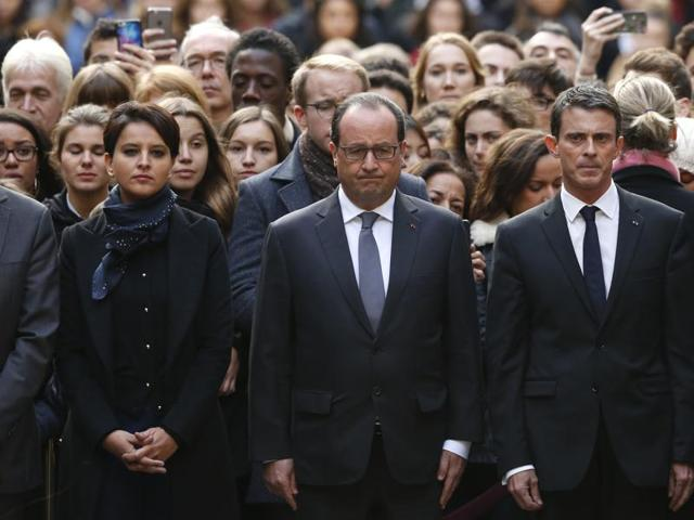 French President Francois Hollande, center, flanked by French Prime Minister Manuel Valls, right, and French education minister Najat Vallaud-Belkacem, center left, stands among students during a minute of silence in the courtyard of the Sorbonne University in Paris.