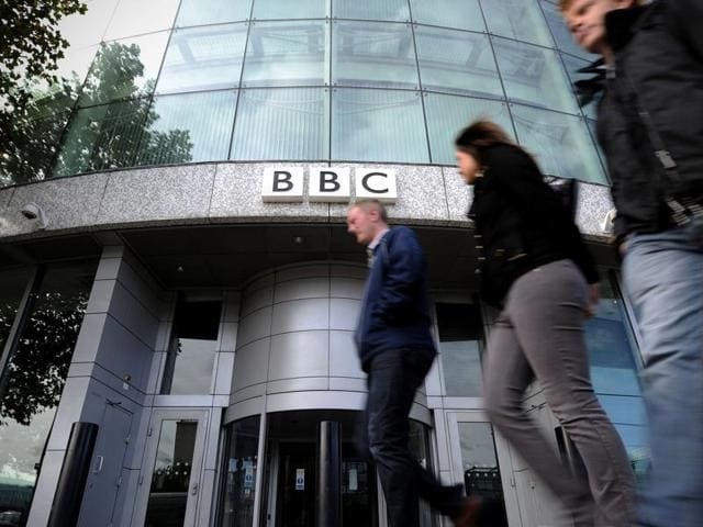 This file picture shows people walking past an entrance to the British Broadcasting Corporation (BBC) Television offices in west London.