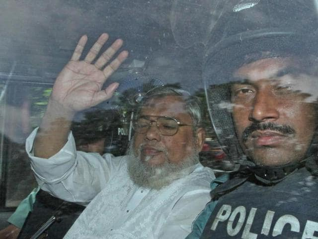 Jamaat e Islam leader Ali Ahsan Mohammad Mujahid (L) waves from a police vehicle as he is transported to the central jail after a court verdict in Dhaka.S