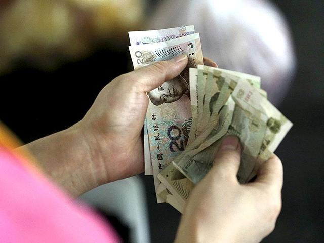 A customer counts Chinese Yuan notes at a market in Beijing.