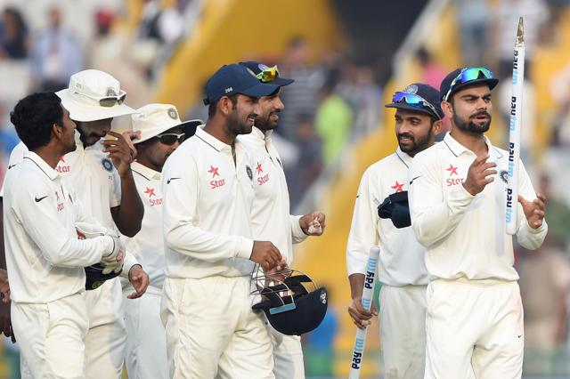 India's captain Virat Kohli (R) with the rest of the squad after winning the first Test against South Africa in Mohali. India lead the four-Test series 1-0.