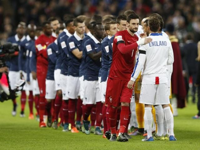 England and France players stand together and observe a minute's silence in honour of the Paris attacks' victims ahead of the start of their friendly at the Wembley on November 17.