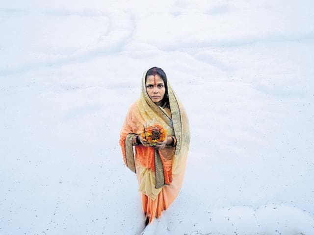 A woman offers prayers to the Sun God on the banks of the Yamuna in Noida.