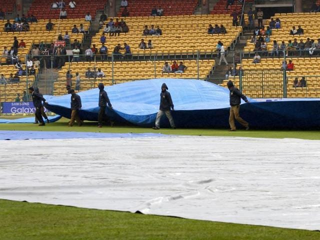 Ground staff cover the outfield as the rain continues during the second Test match between India and South Africa in Bengaluru, on November 17, 2015.