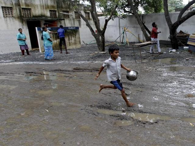 A boy runs with a utensil to collect food at a temporary shelter for those affected by floods following heavy rains in Chennai, Tamil Nadu. Heavy rains across Andhra Pradesh claimed the lives of at least 6 people, even as northeast monsoon relented in Tamil Nadu.(AP Photo)