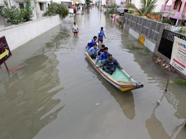 Rescue workers on a boat move people to safety at a residential area in rain-hit  Chennai .