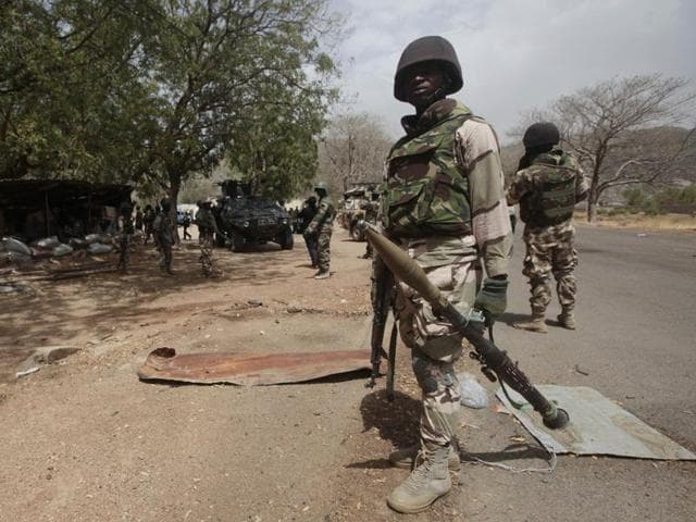 In this file photo, Nigerian soldiers man a checkpoint in Gwoza, Nigeria. An explosion, suspected to be triggered by extremist group Boko Haram, ripped through northwestern Nigeria, killing dozens and injuring many.