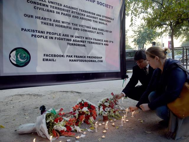 Members of the Pak-France Friendship Society place candles during a vigil to pay tribute to victims of the Paris attacks claimed by Islamic State.