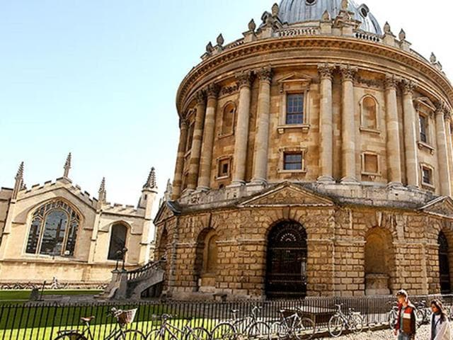 Students walk past the Radcliffe Camera building in Oxford city centre at Oxford University, in Oxford.