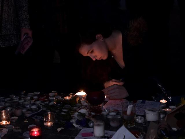 Women light candles, as thousands of people gather at the central square in Strasbourg, eastern France.