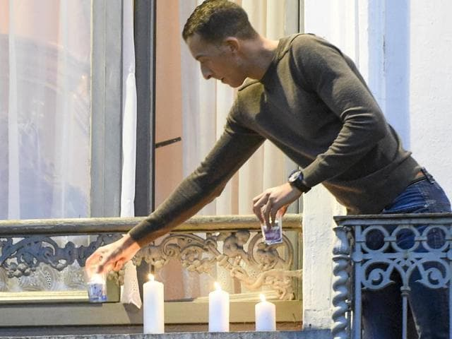 Mohamed Abdeslam, brother of Brahim Abdeslam, an attacker who died in the Paris assault, places candles on the balcony of his house in the Brussels suburb of Molenbeek during a memorial gathering to honour the victims of the recent deadly Paris attacks, in Brussels, Belgium.