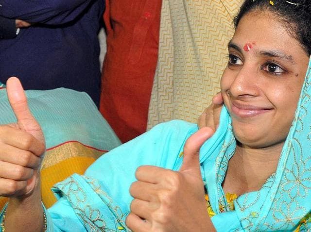 Geeta waves to the media after her arrival at Indore airport from Delhi.