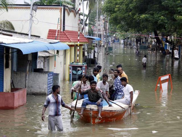 People gather around a residential area that was flooded after heavy rains in Chennai on November 18, 2015.