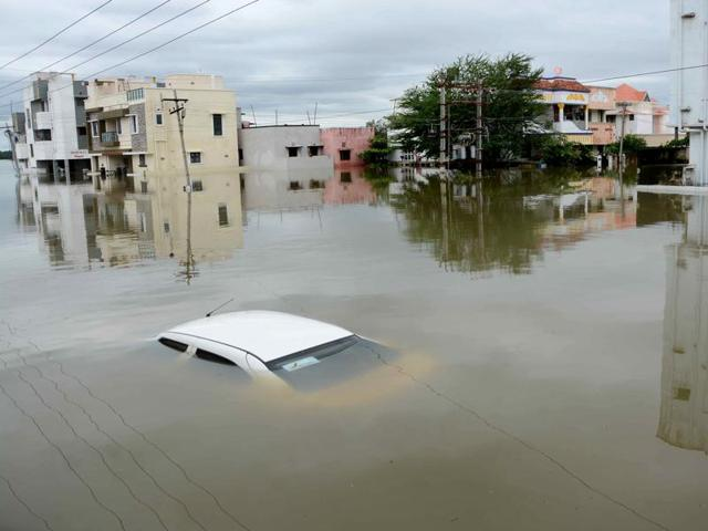 A car is submerged amidst water-logged houses in a rain-hit area of Chennai.