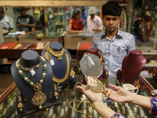 A customer tries a gold necklace at a jewellery showroom on the occasion of Dhanteras, a Hindu festival associated with Lakshmi, the goddess of wealth, at a market in Mumbai.