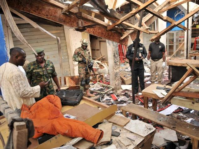 Soldiers and policemen are pictured at the scene where two female suicide bombers blew themselves up at a mobile phone market in the northern Nigerian city of Kano.