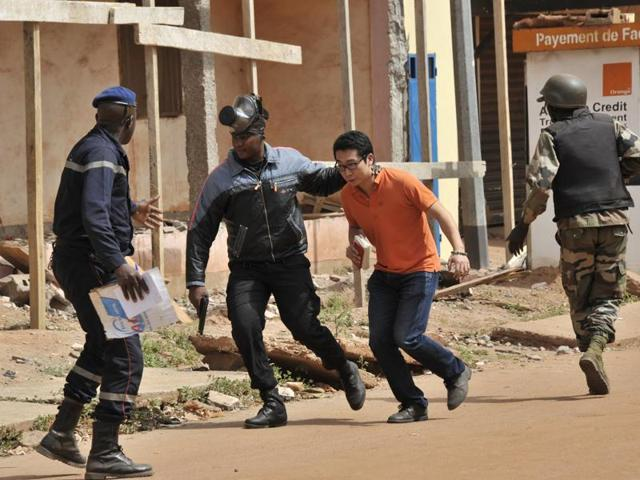 Malian security forces evacuate a man from an area surrounding the Radisson Blu hotel in Bamako.