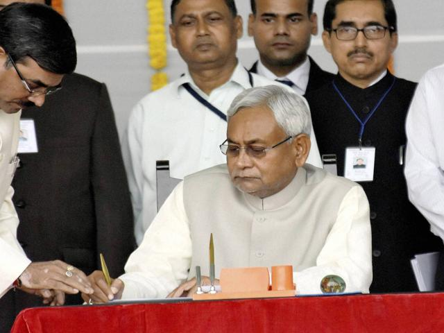 Nitish Kumar signing the register after taking oath as the chief minister of Bihar at Gandhi Maidan in Patna on Friday.