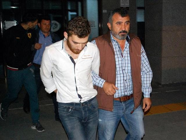 A 26-year old Belgian citizen Ahmet Dahmani is escorted by a plain clothes police officer on November 20, 2015 in Antalya. Turkish police have arrested a Belgian man of Moroccan origin on suspicion he scouted out the target sites for Islamic State in attacks that killed 129 people in Paris a week ago.
