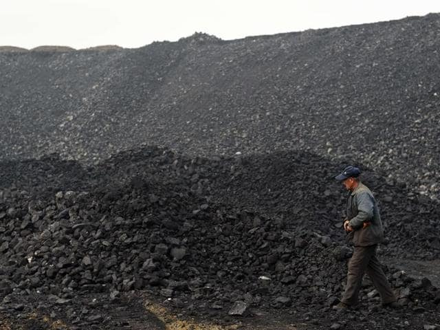 A worker walks past a pile of coal near a coal mine in Datong, in China's northern Shanxi province. A fire at a coal mine in the province of Heilongjiang killed several.