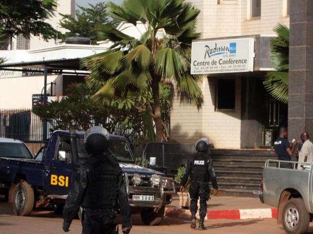 Mali police walk outside one of the entrances to the Radisson Blu hotel's conference center after an attack by gunmen on the hotel in Bamako, Mali.