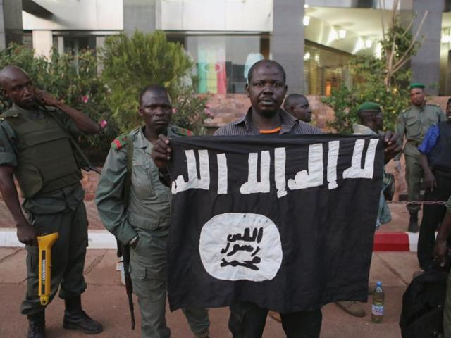 Malian security officials show a flag they said belonged to attackers in front of the Radisson hotel in Bamako, Mali.