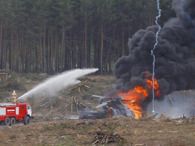 Firefighters work to extinguish fire, which overtook a Mi-28N from the Berkuty (Golden Eagles) helicopter display team after a hard touchdown during the