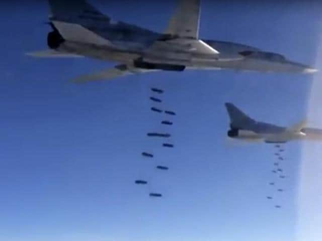 In this photo made from video released from Russian Defense Ministry official website, Russian air force Tu-22M3 bombers drop bombs on a target in Syria as part of a Russian air campaign against targets in Syria, according to information provided by Russian Defense Ministry.
