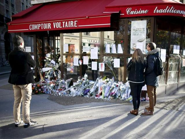 People stop to look at flowers, candles and messages in tribute to victims in front of the Comptoir Voltaire cafe, one of the sites of the deadly attacks in Paris.