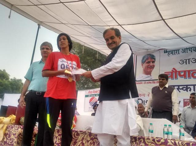 Union rural development minister Birender Singh giving away a prize to a winner of 'Chaupal marathon' held at Baiyanpur village in Sonepat on Sunday.