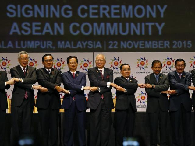 ASEAN leaders join their hands as they pose for photographers after the signing ceremony of the 2015 Kuala Lumpur Declaration on Establishment of the ASEAN Economic Community.