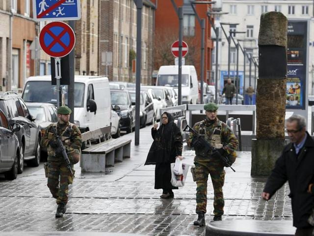 A police officer and a soldier patrol on the Anspach boulevard on November 22, 2015 in Brussels. Security was tightened in Belgium with the capital on maximum alert following the fatal attacks in Paris.