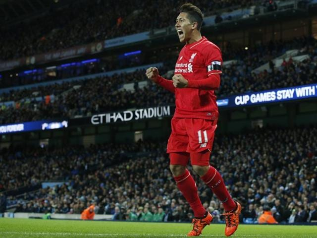 Liverpool's Roberto Firmino celebrates with teammate Philippe Coutinho after Manchester City's Eliaquim Mangala scores an own goal during the EPL match at the Etihad Stadium on November 21, 2015.