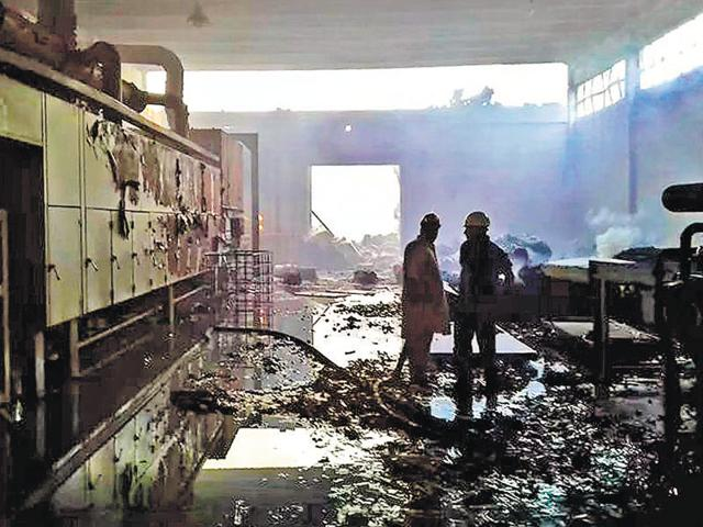 Pakistani firefighters stand in a burnt out factory torched by an angry mob in Jehlum.