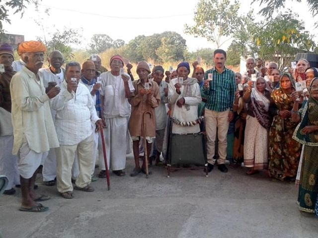 Inmates of an old age home in Dewas show their voter ID cards on Saturday.