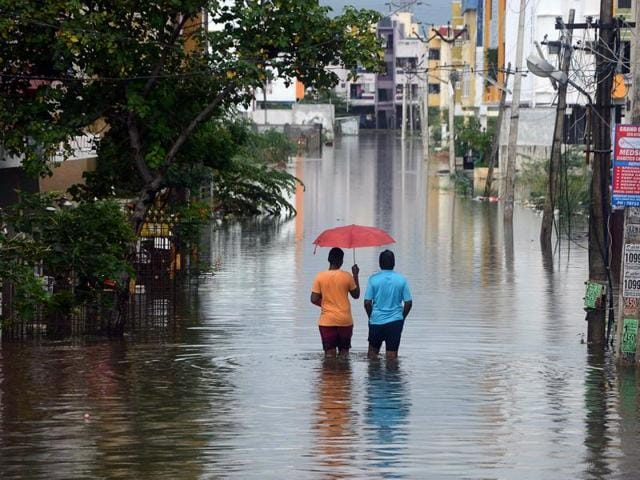 Indian men make their way on a flooded street following heavy rain in Chennai on November 16, 2015. Large areas of the southern Indian city of Chennai have been flooded following days of heavy rain.