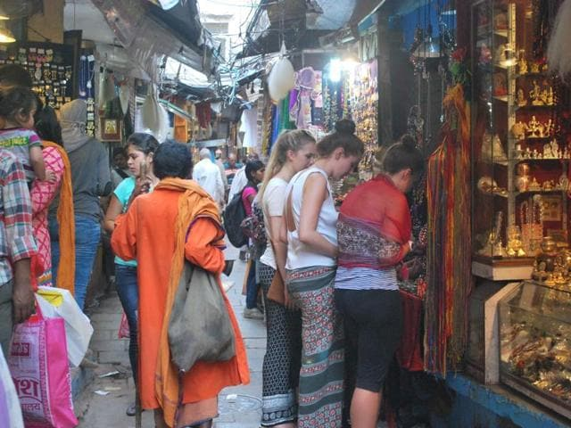 Foreign tourists in a lane near the Kashi Vishwanath temple in Varanasi. The trust of the temple has issued an order asking foreign tourists in short dresses to wear a sari or dhoti and 'anga vastram' before entering the sanctum sanctorum.