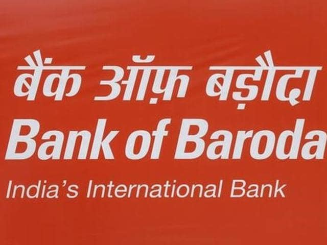 Commuters walk past an advertisement of Bank of Baroda at a busy street in New Delhi.