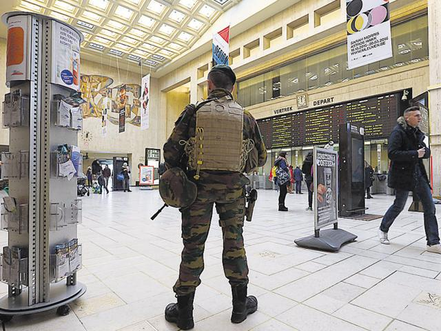 A soldier stands near of the departures board as he patrols Brussels Central Station.