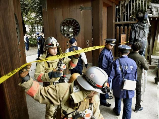 Police officers and fire fighters investigate at the south gate of Japan's controversial Yasukuni Shrine where there was an explosion and burned the ceiling and wall of the public bathroom, in Tokyo, Japan.