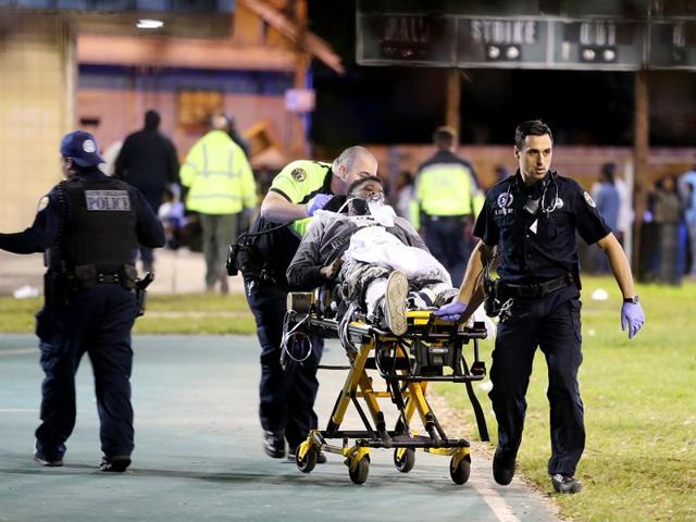 Paramedics with New Orleans EMS remove a man from the scene following a shooting in New Orleans.