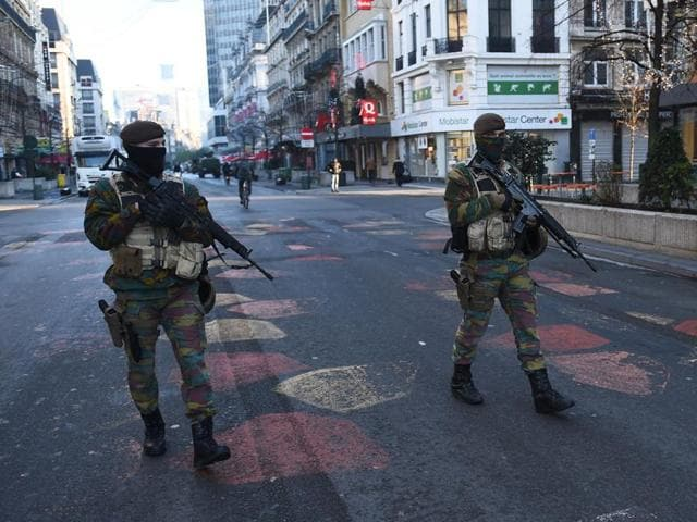 Belgian troops patrol a street in Brussels as the Belgian capital remains on the highest possible alert level.