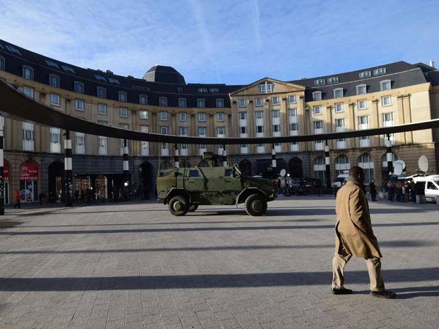 A man walks by an armoured vehicle as the Belgian capital remains on the highest possible alert level, in Brussels.