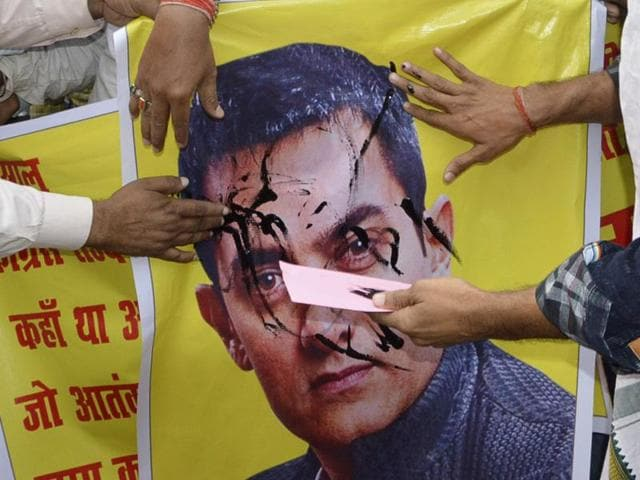 BJP activists burn a poster of Bollywood actor Aamir Khan as they protest over his remarks on intolerance in the country, in Patna.
