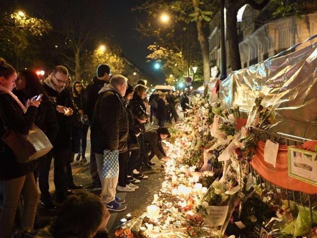 People gather at a makeshift memorial in tribute to the victims of a series of deadly attacks in Paris.