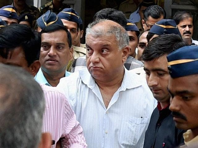 Peter Mukerjea is escorted after being produced by the CBI at the Esplanade court in Mumbai on Friday.